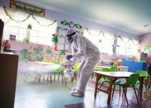 A man disinfecting a classroom as part of reopening daycare facilities post-COVID-19