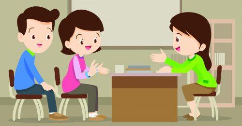 Parent meeting with teacher in classroom.